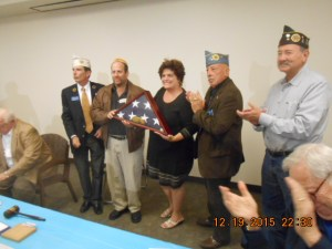 Commander Greg Lee presents the American Flag to Rosie and Frank Rubin.
